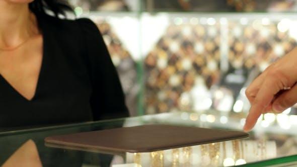 Thumbnail for Schmuck-Shop, ein Paar Trauringe im Schaufenster, Verkäufer Berater demonstriert Ringe Kunde