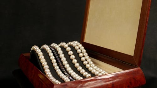 Pearl Bracelets In Brown Wooden Casket, Jewelry Made Of Pearls, Pearl Bracelets On a Pedestal