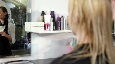 Hairstylist combing client hair