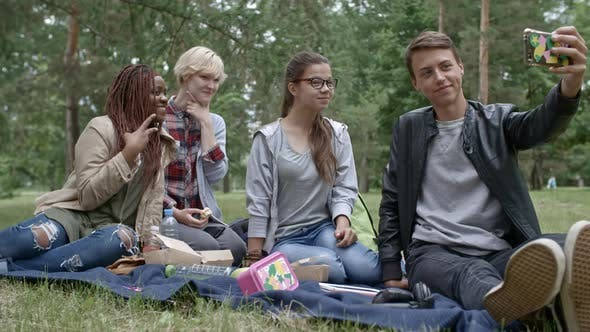 Thumbnail for Cheerful Teens Taking Selfie on Smartphone at Picnic