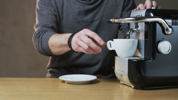 Thumbnail for A Man Takes a Cup Out Of The Coffee Machine