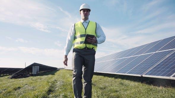 Thumbnail for Man In Vest Walking Near Solar Panels