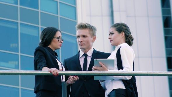 Thumbnail for Drei Mitarbeiter stehen auf der Terrasse des Bürogebäudes und Sprechen