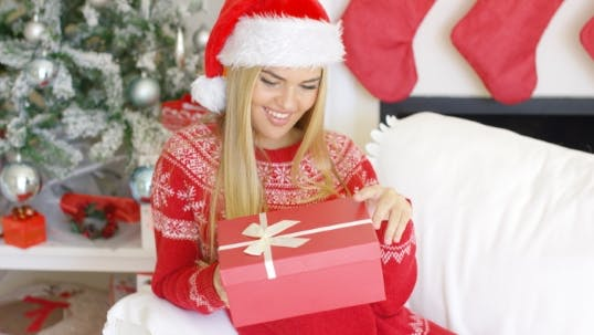 Thumbnail for Pretty Smiling Blondie Looking At Her Boxed Christmas Gift