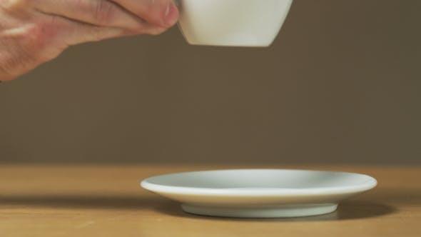 A Man Puts a Cup On a Saucer