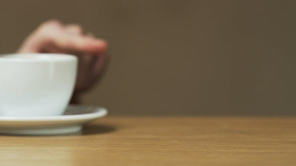 Thumbnail for A Man Pushes The Saucer With a Cup