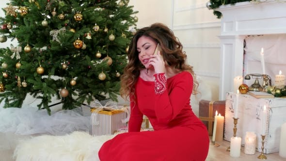 Thumbnail for Christmas, Girl In Festive Attire, Talking On a Cell Phone, Sitting In The Living Room Near The