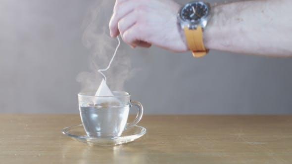 Man Puts a Teabag Into a Cup