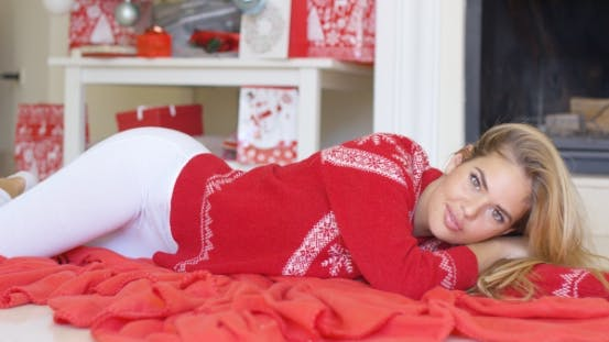 Thumbnail for Young Happy Girl Lying On Red Blanket Next To Fireplace