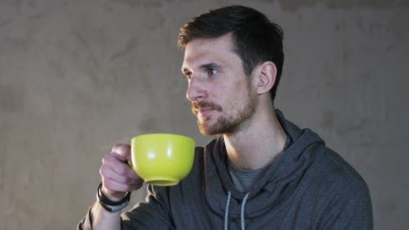 Thumbnail for Young Man Drinks Tea From A Green Cup