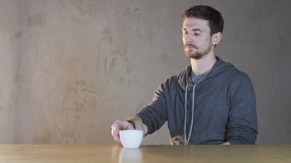 Thumbnail for Young Man Drinks Tea From A White Cup
