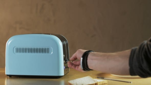 Thumbnail for Man Puts Two Loaves Of Bread Into An Electric Toaster