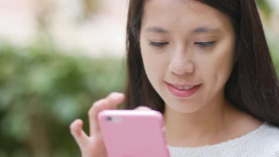 Thumbnail for Woman sending sms on cellphone at outdoor