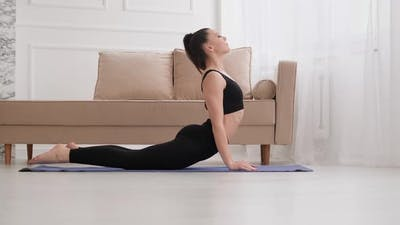 Woman Practicing Yoga Exercise in Living Room