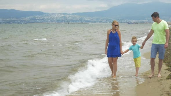 Thumbnail for Family With Child Walking Along The Shore