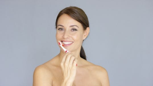 Thumbnail for Attractive Smiling Woman Brushing Her Teeth