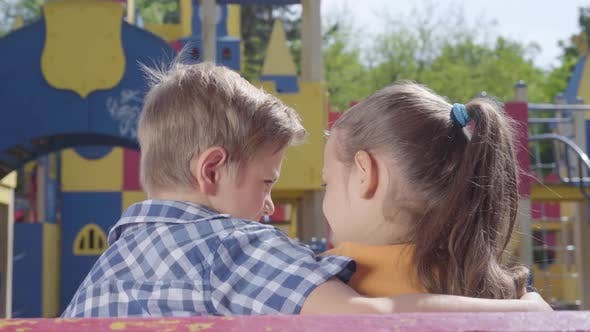 Thumbnail for Cute Blond Boy and a Pretty Girl Sitting on the Bench in Front of the Playground Hugging. A Couple