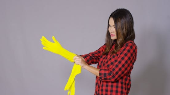 Thumbnail for Young Housewife Putting On Rubber Gloves