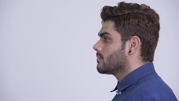 Thumbnail for Closeup Profile View of Young Bearded Indian Businessman Looking at Camera