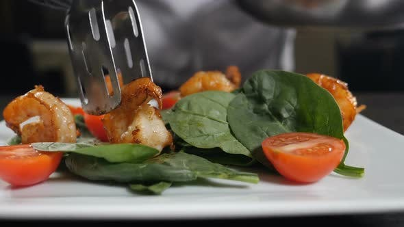 Thumbnail for Hand Puts Shrimp on Salad with Tongs. Chef Finishing Dish Adding Fried Prawn To Fresh Vegetarian
