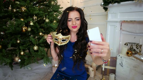 Thumbnail for Masquerade Girl Makes Selfie At a Christmas Party Near The Christmas Tree, New Year Celebration In