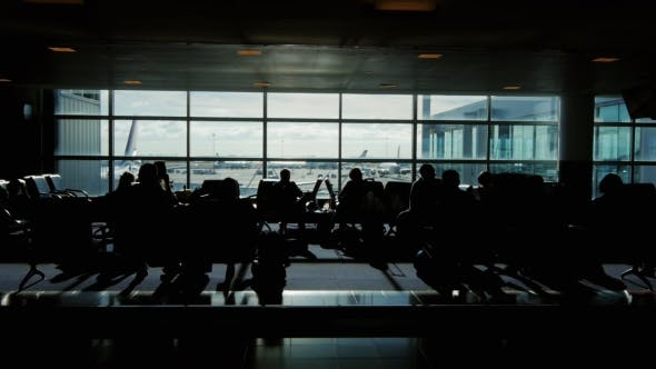 Cover Image for Tracking Shot Of a Large Airport Terminal. Silhouettes Of Passengers Waiting For Their Flight