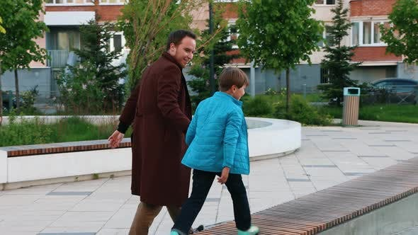Thumbnail for Young Man and His Little Brother Walking in Square Near the House