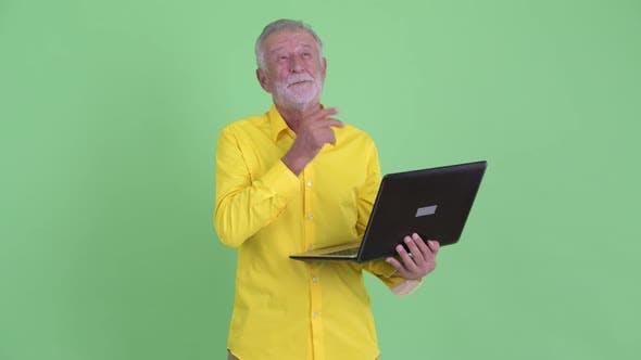 Thumbnail for Happy Senior Bearded Businessman Thinking While Using Laptop