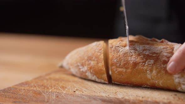 Female Baker Cutting Homemade Bread at Bakery