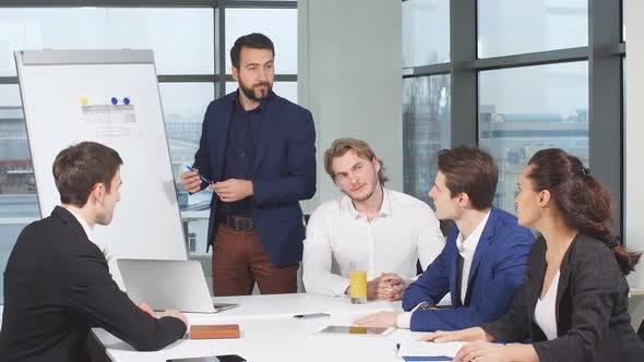 Group of Young Businessmen in Stylish Suits at Table in Office Discuss Project