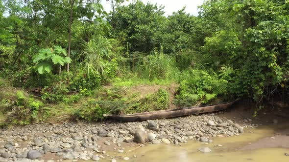 Thumbnail for Zooming out on a large wooden canoe that lays on a riverbed of a large tropical river