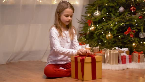 Thumbnail for Happy Girl Opening Christmas Gift at Home