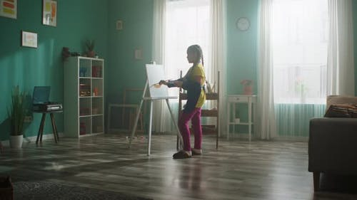 Small Girl Student Is Painting at Home