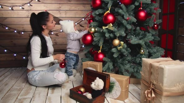 Cover Image for Mother And Adorable Baby Decorating a Fir-tree
