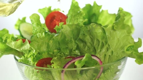 Öl auf grünen Salat gießen
