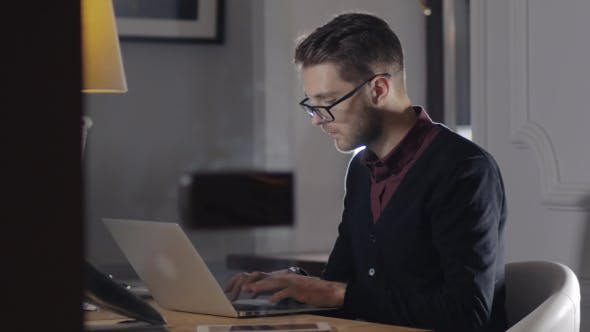 Thumbnail for Multitasking. Handsome Young Man Wearing Glasses And Working Withlaptop While Sitting In Modern