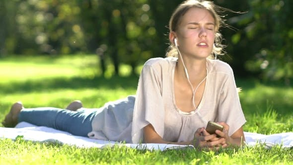 Thumbnail for Young Woman Listening To Music And Using Smartphone In The Park