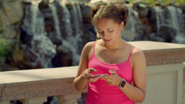 Thumbnail for Girl Watching Photos On Smart Phone. Latin Girl Using Phone At Park