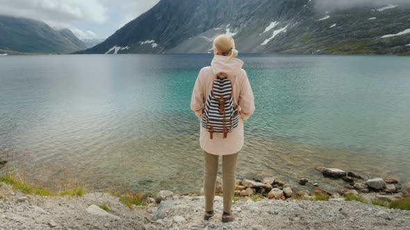 Thumbnail for A Woman Admires a Beautiful High Mountain Lake in the Mountains of Norway. Crane Shot