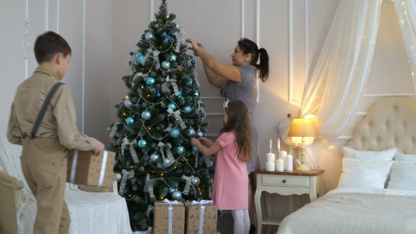 Thumbnail for Footage Family Decorating a Christmas Tree For The Holiday.