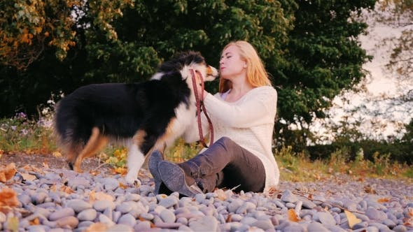 Thumbnail for Young Woman Caresses Her Dog. Sitting On a Beach Of Pebbles, Stroking Her Australian Shepherd