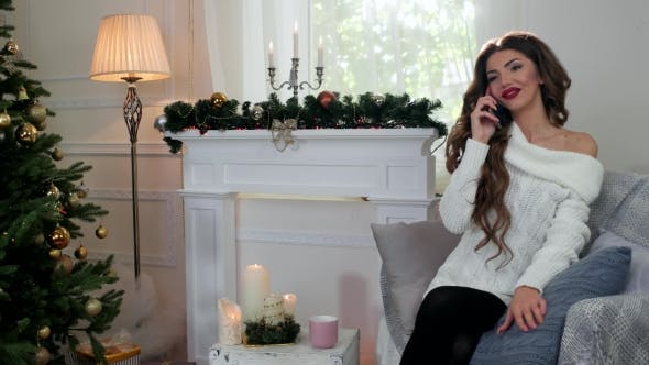 Thumbnail for Young Nice Girl Speaks By Mobile Phone In Sitting In The Living Room On a Sofa Near Christmas Tree