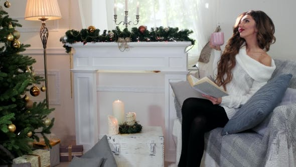 Cover Image for Winter Holidays, Girl Reading a Book, Woman Drink Tea From a Cup, In Cozy Clothes, Sitting By The