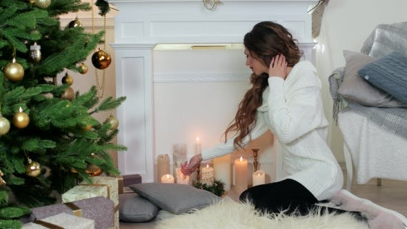 Lighted Candles, Beautiful Young Woman In The Warm Cozy Sweater Lights a Candle