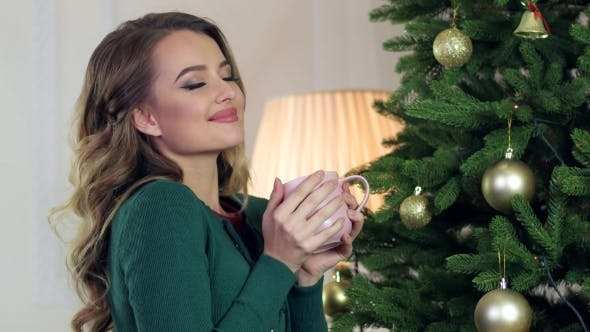 Thumbnail for Happy Girl Drinks Tea, Smiling Looks Into The Camera, In The Living Room Near Christmas Tree