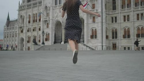 Excited Girl Running to Parliament of Budapest Hungary