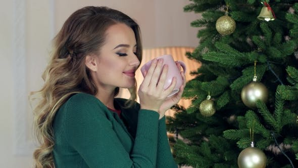 Girl Drinks Tea From a Cup In The Living Room Near Christmas Tree, Portrait Of a Young Woman