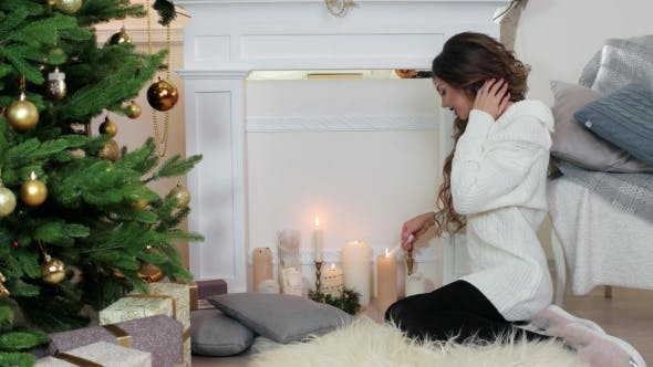 Cover Image for Christmas, Girl Lights a Candle Sitting By The Fireplace Near The Christmas Tree, Beautiful Young