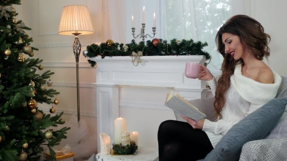 Thumbnail for A Girl Reads a Book, a Young Woman Drinking Tea While Sitting On The Couch By The Fireplace