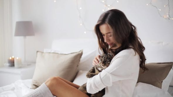 Thumbnail for Happy Young Woman With Cat In Bed At Home 1